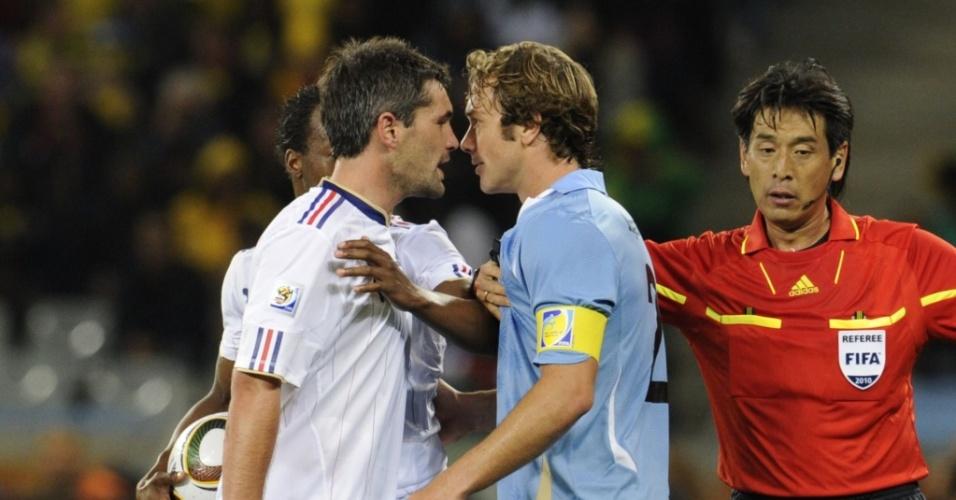Francês Jeremy Toulalan (e) e uruguaio Diego Lugano se desentendem, e o árbitro Yuichi Nishimura tenta separar