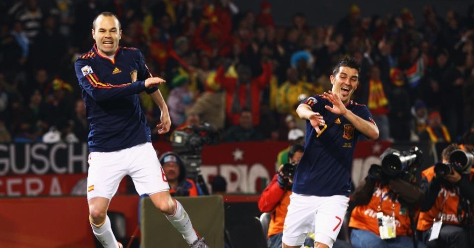 Iniesta dá uma tapa na bandeira de escanteio e David Villa se protege após gol da Espanha