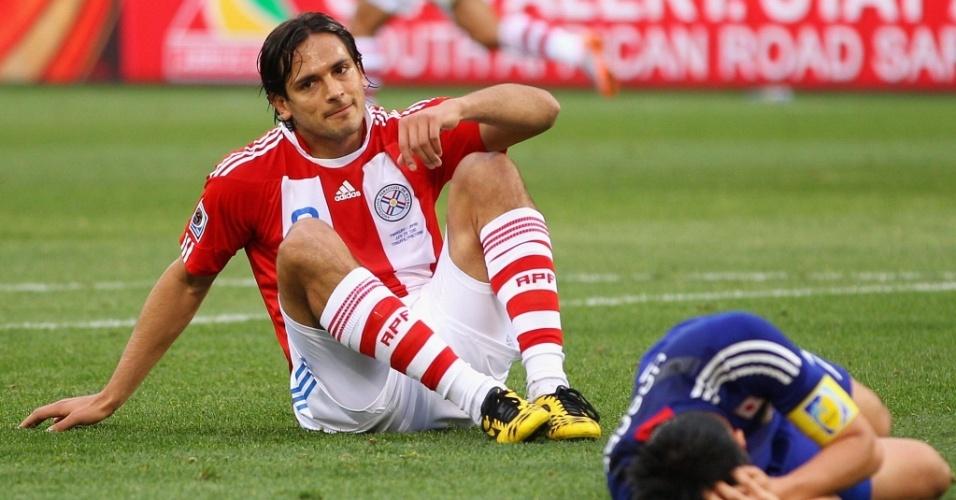Roque Santa Cruz sentado no gramado após mais uma chance perdida pelo Paraguai no jogo contra o Japão