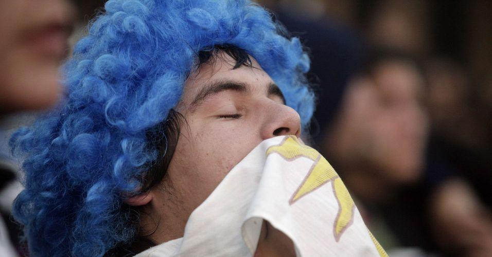 Torcedor Uruguaio se cobre com a bandeira enquanto assiste à derrota na Praça da Independência, em Montevidéu