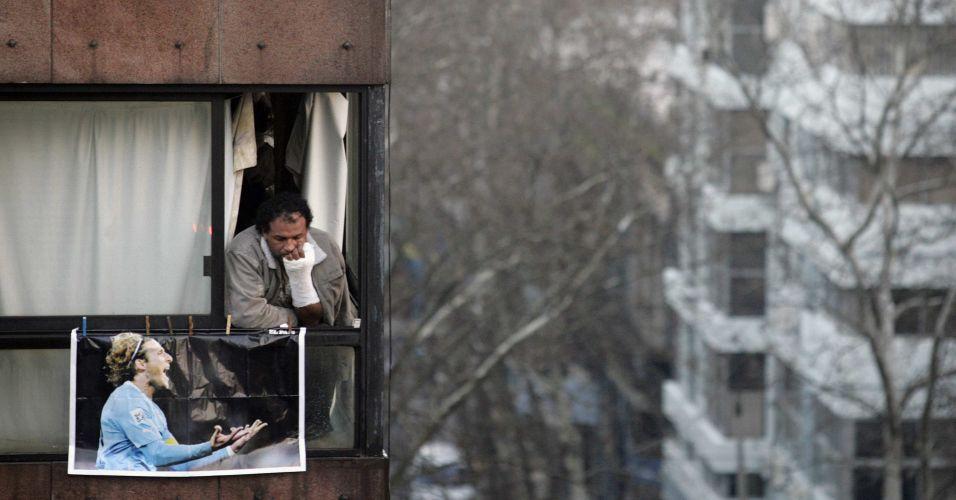 Ao lado de um pôster de Forlán, uruguaio lamenta na janela de seu apartamento a eliminação na Copa diante da Holanda