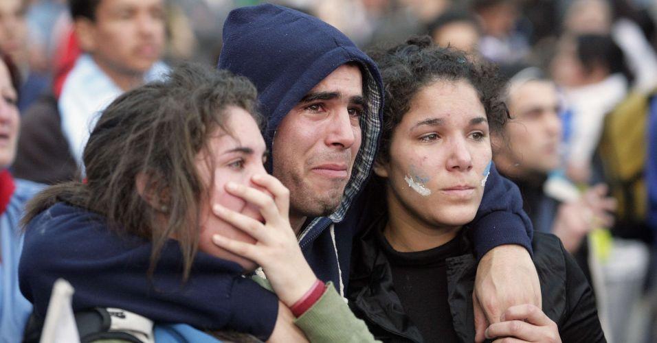Torcedores uruguaios choram eliminação enquanto assistem à derrota na Praça da Independência, em Montevidéu