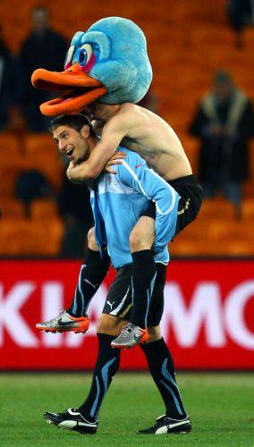 Sebastian Eguren carrega Diego Perez após o Uruguai eliminar Gana nos pênaltis e se classificar para as semifinais da Copa do Mundo (julho/2010)