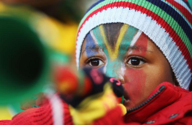 Mesmo na partida entre Grécia e Nigéria, pequeno torcedor veste as cores da África do Sul e assopra vuvuzela