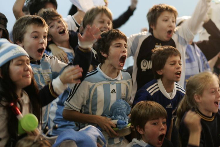 Ao ver o gol pela teve, pequenos torcedores vibram em Buenos Aires com um dos quatro gols argentinos na vitória sobre a Coreia do Sul, pelo grupo B