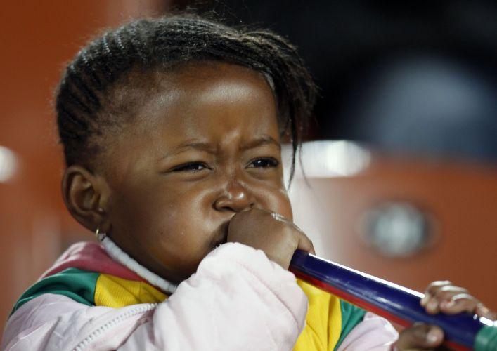 Pequena torcedora se esforça para tocar vuvuzela em partida pela segunda rodada da Copa do Mundo