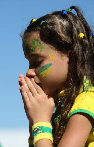 Garotinha reza em Copacabana, no Rio de Janeiro, mas seleção brasileira não corresponde e está fora da Copa do Mundo