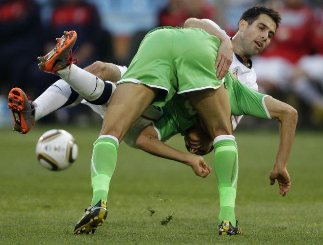 Argelino Matmour (de verde) fica em posição constrangedora em disputa de bola com o norte-americano Bocanegra durante jogo da Copa do Mundo (junho/2010)
