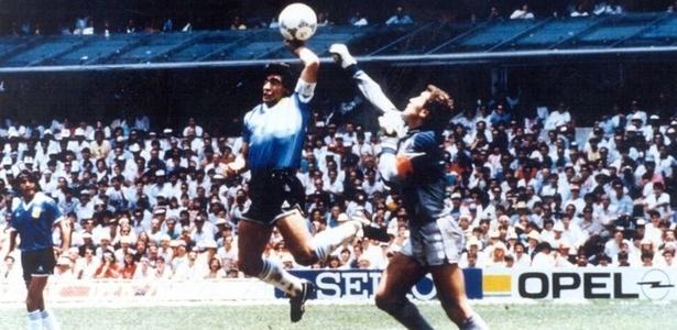 Maradona salta e usa a mão para empurrar a bola para dentro do gol inglês