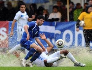 Jogadores de Honduras e Azerbaijão disputam a bola no campo cheio de poças d'água