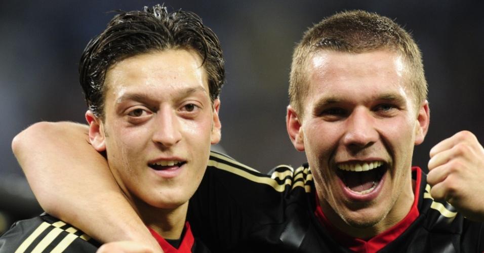 Alemães Mesut Oezil e Lukas Podolski celebram a goleada sobre a Argentina e a classificação às semifinais da Copa
