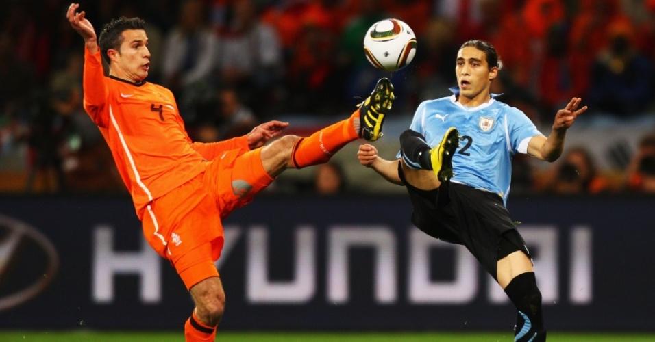 O holandês Van Persie domina a bola, sob o olhar do uruguaio Cáceres