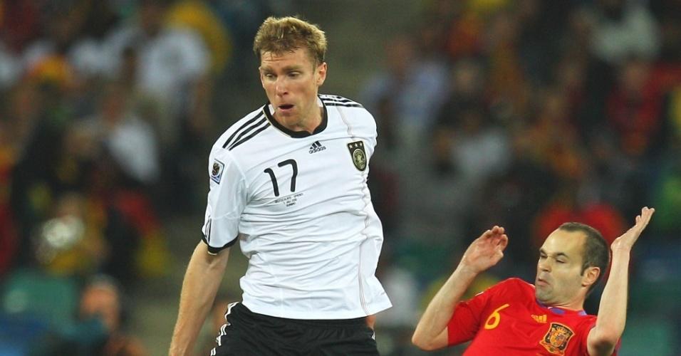 Mertesacker (e) disputa a bola com Iniesta no jogo Alemanha x Espanha