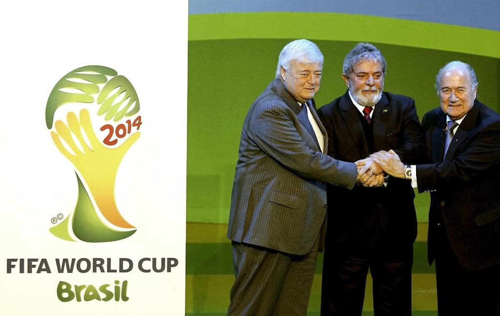 Ricardo Teixeira, Lula e Joseph Blatter cumprimentam-se ao lado da logomarca da Copa de 2014