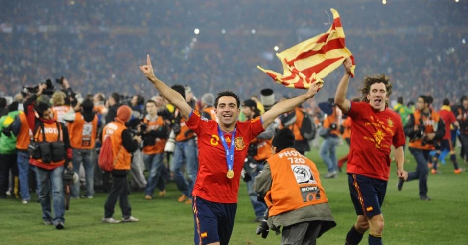 Após a conquista do título da Copa, Xavi (e) e Puyol correm pelo gramado do Soccer City com uma bandeira da Catalunha