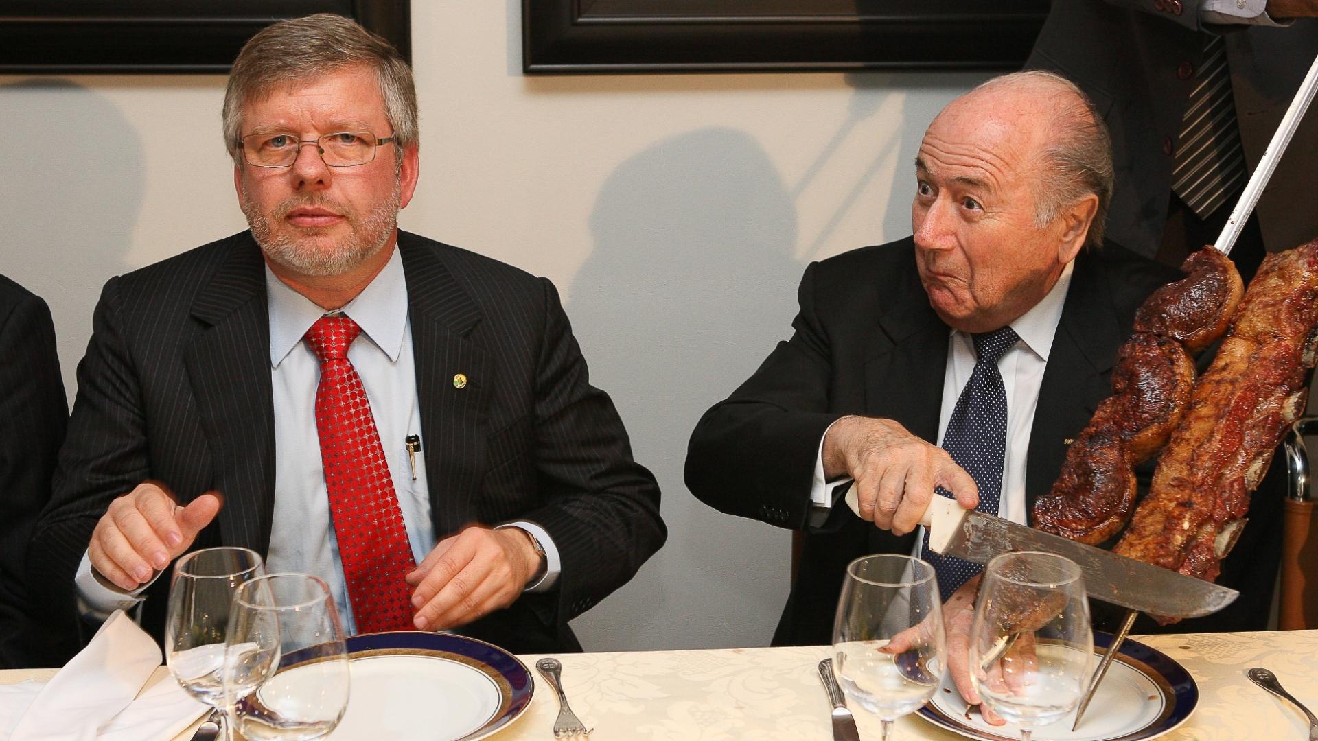 Joseph Blatter, presidente da Fifa, faz careta ao cortar carne oferecida a ele em almoço na casa do presidente da Câmara, o deputado Marco Maia (PT-RS)