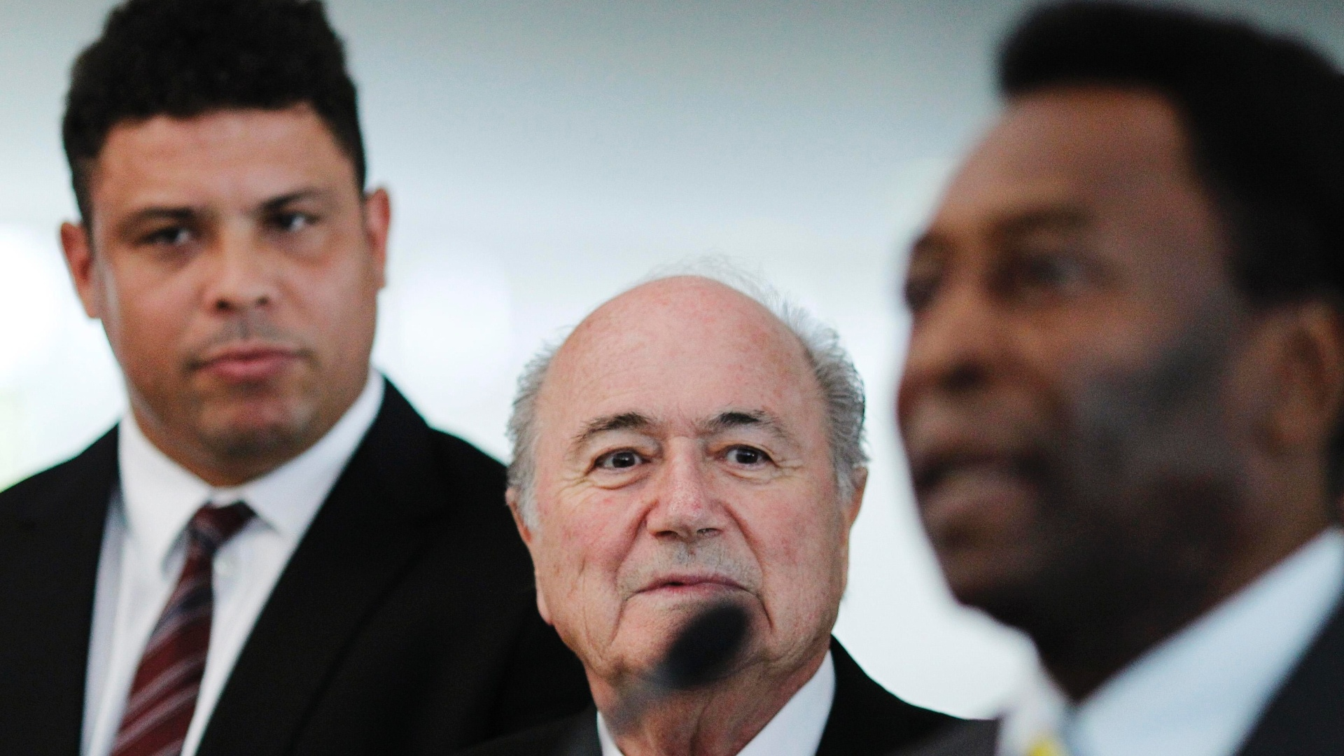 Ronaldo observa Joseph Blatter e Pelé em conversa com a imprensa após uma reunião em Brasília